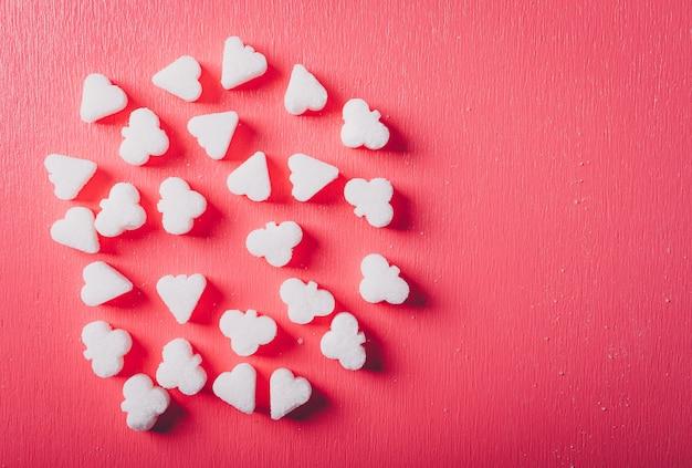 Vista superiore dello zucchero bianco su una tavola di rosa rosso