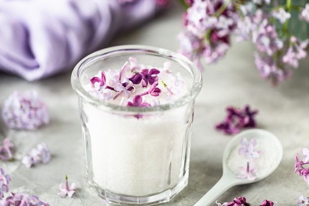 White sugar with lilac flowers on a marble background.
