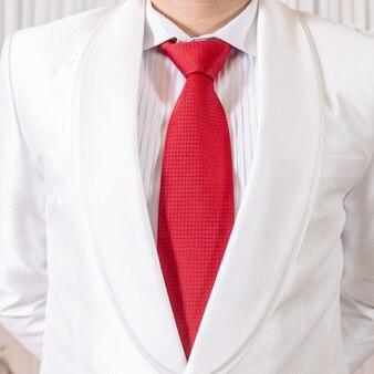 Белый костюм и красный галстук