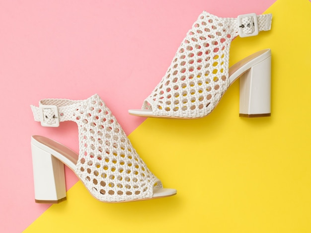 White summer fashion women shoes on pink and yellow surface
