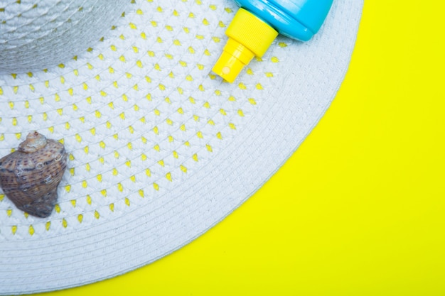 On a white sun hat with a wide brim there is a shell and a tanning agent on a yellow background with...