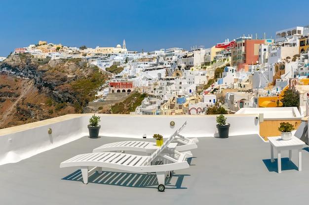 Белые шезлонги для отдыха на веранде в фире, современной столице греческого острова эгейского моря, санторини, греция