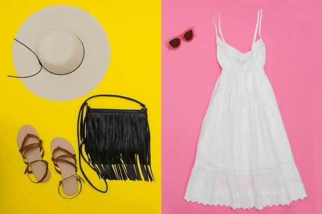 白いサンドレス、黒いハンドバッグ、茶色の靴、サングラス。鮮やかなピンクと黄色の表面