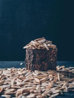 Белые семена подсолнуха в деревянный огрызок и вокруг на черном фоне. вид сбоку. место для текста