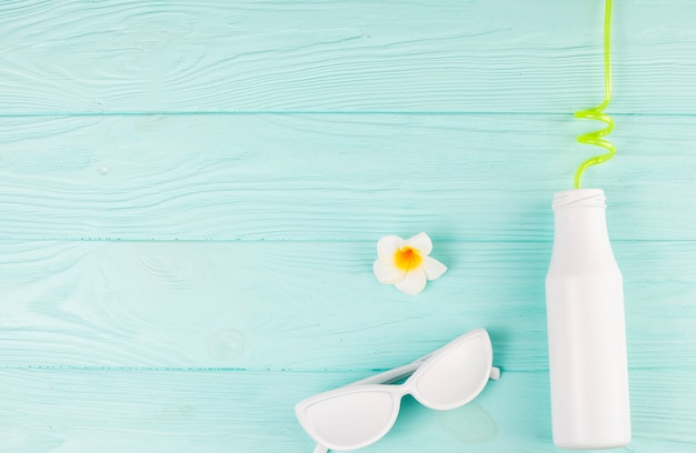 White sunglasses and bottle with straw