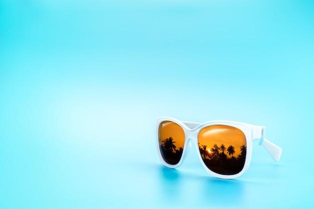 White sunglasses reflection sunset at palm tree landscape scene in light blue studio
