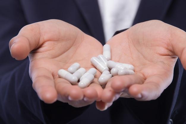 백색 보충제 제품. 캡슐을 들고 여자 손의 근접 촬영입니다. 건강한 다이어트 영양 개념.