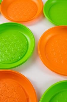 白い表面。有害なプラスチック製で生態学的災害を引き起こす危険な緑とオレンジの使い捨てプレート