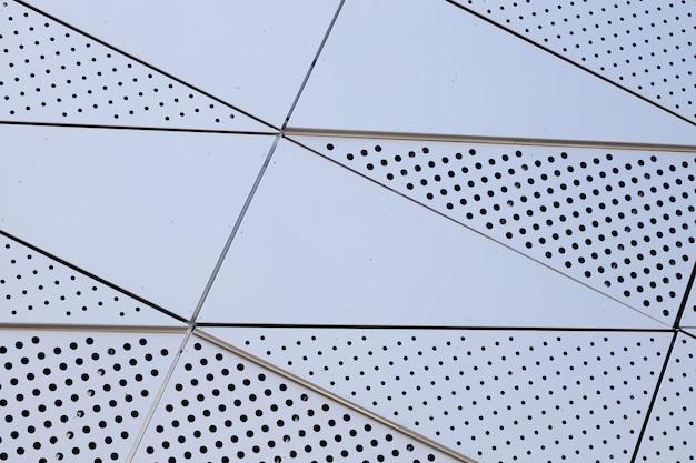 둥근 구멍이있는 금속 벽의 흰색 표면
