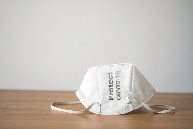 Covid-19やコロナウイルス、汚染のほこり、バクテリアから身を守るために着用する木製のテーブルに白い手術用フェイスマスク。ヘルスケアと外科の概念。 Premium写真