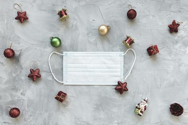 Белая хирургическая маска для рта и красное украшение рождественского праздника. карантин, изоляция и коронавирус covid-19, празднование праздников, социальное дистанцирование и концепция зимнего сезона