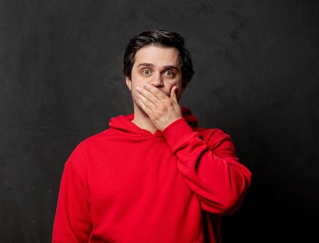 Белый удивленный парень в красной толстовке на темной стене