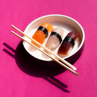 White sushi bowl with chopsticks on rose background