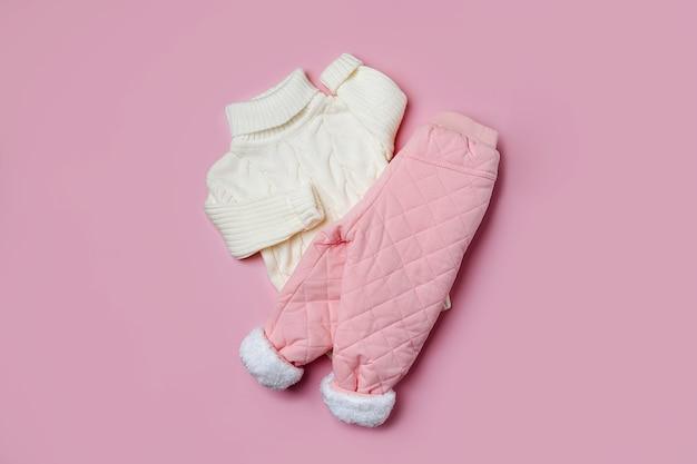 분홍색 배경에 흰색 스웨터와 따뜻한 바지. 스타일리시한 아동복. 겨울 패션 복장