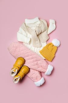 분홍색 배경에 모자와 부츠가 달린 흰색 스웨터와 따뜻한 바지. 스타일리시한 아동복. 겨울 패션 복장