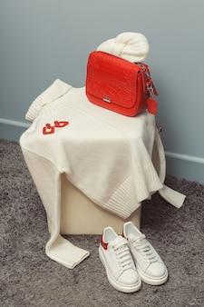 白いセーター、白い切り身、赤いイヤリング、革のバッグ。