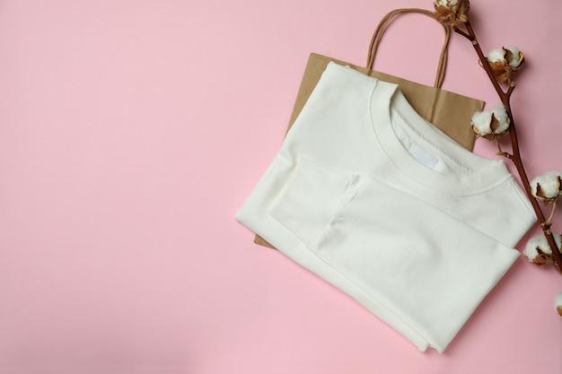 ピンクの背景に白いスウェットシャツ、バッグ、コットン