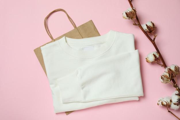 Белая толстовка, сумка и хлопок на розовой поверхности