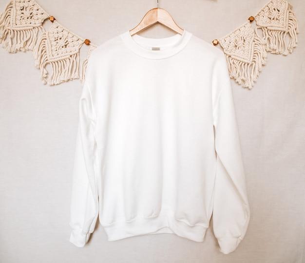 옷걸이에 흰색 운동복 모형 boho 배경으로 빈 까마귀 모형