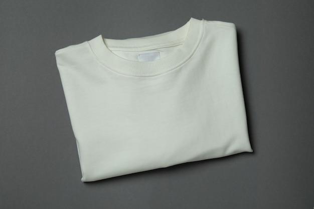 灰色の背景に白いスウェットシャツ