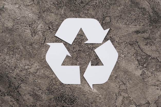 White symbol of recycling on dirty background