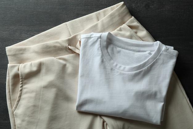 어두운 나무에 흰색 티셔츠와 스웨트 팬츠