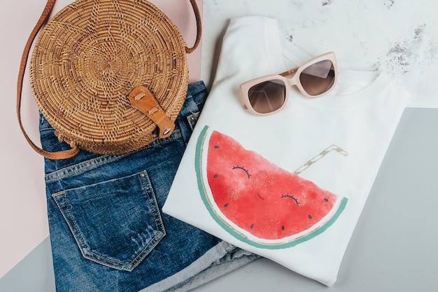 White t-shirt, blue denim shorts, fashionable organic rattan bag, sunglasses