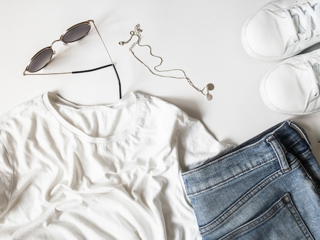 White t-shirt blue jeans, sunglasses, necklace and white sneakers on white background.