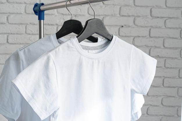 レンガの壁にハンガーに掛かっている白いtシャツ