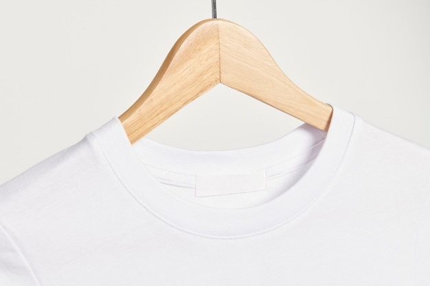 Белая футболка на деревянной вешалке