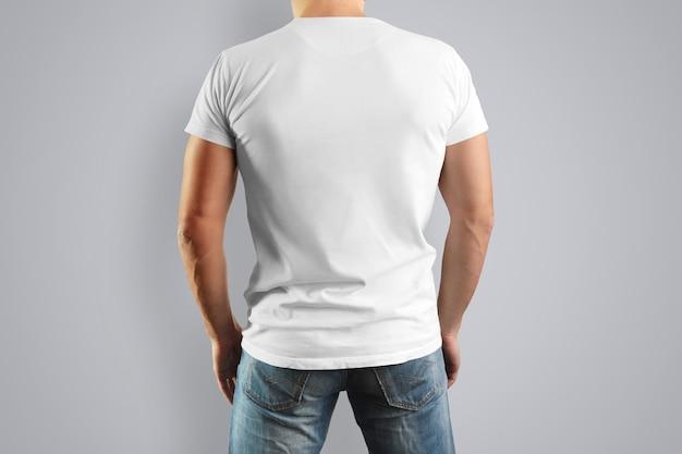 後ろから若いカビの景色に白いtシャツ。灰色の壁に隔離。