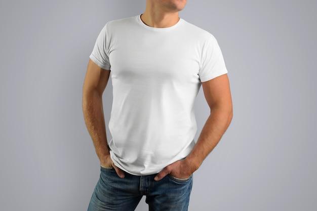 灰色の壁に隔離された若い筋肉質の男の白いtシャツ。
