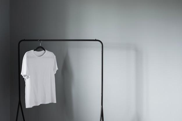 灰色の壁に黒いハンガーの白いtシャツ