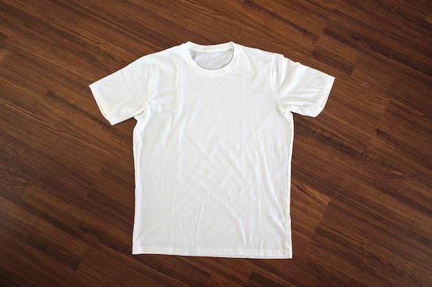 木製の床に白いtシャツ
