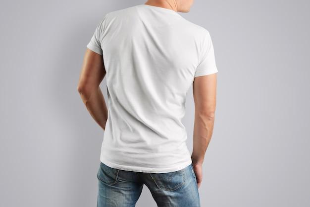 ブルージーンズと筋肉質の男性の背面図の白いtシャツ。