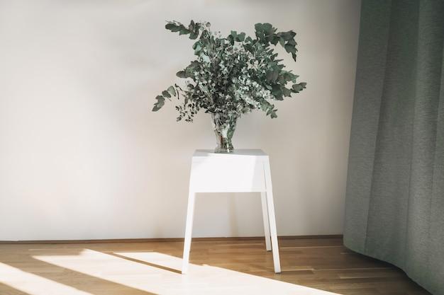 유칼립투스 나뭇가지가 있는 흰색 테이블과 유리 꽃병