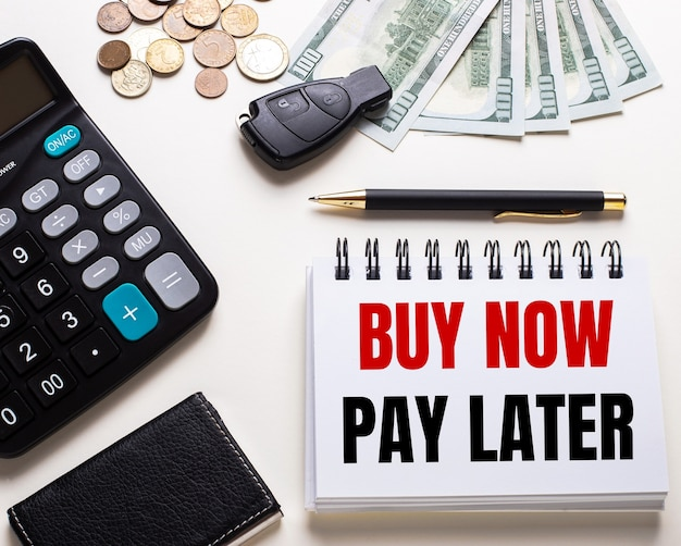 On a white table is a calculator, car key, cash, a pen and a notebook with the inscription buy now – pay later