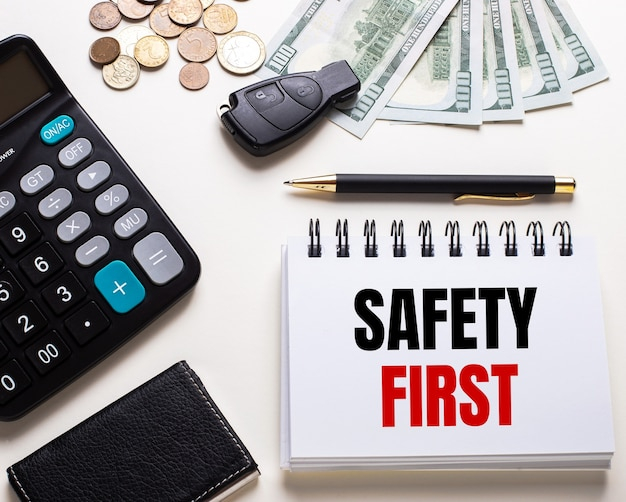 On a white table is a calculator, car key, cash, a pen and a notebook with the inscription safety first