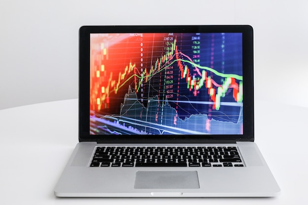 On a white table laptop with a graph of growth
