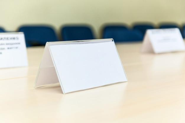 Белые таблички на столе для участников конференции