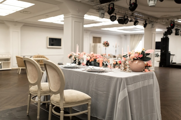 The white table in the restaurant is decorated with fresh flowers. stylish event decor