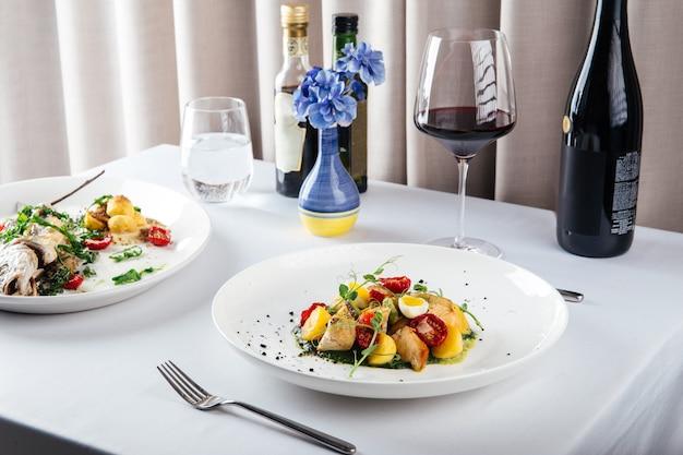 白いテーブルで美味しいイタリア料理と赤ワイン、水平