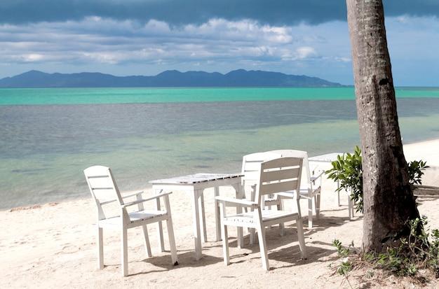 바다를 향한 모래 해변에 흰색 테이블 설정