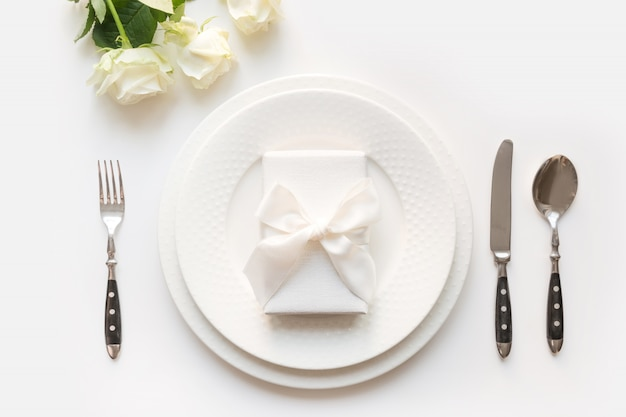 White table setting with bouquet rose, gift, dishware, silverware on white table. romantic and wedding anniversary.
