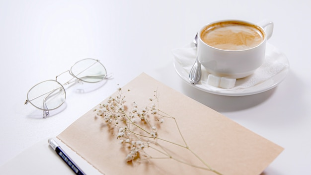 On a white table there is a cup of coffee, glasses, a notebook with a pencil and a white flower.