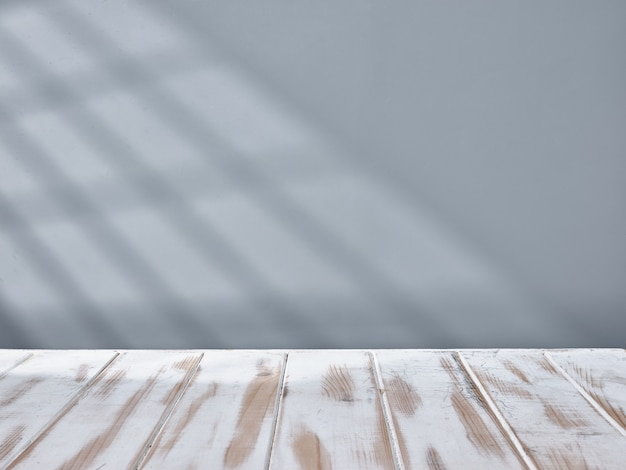 White table top and gray wall with light from the window