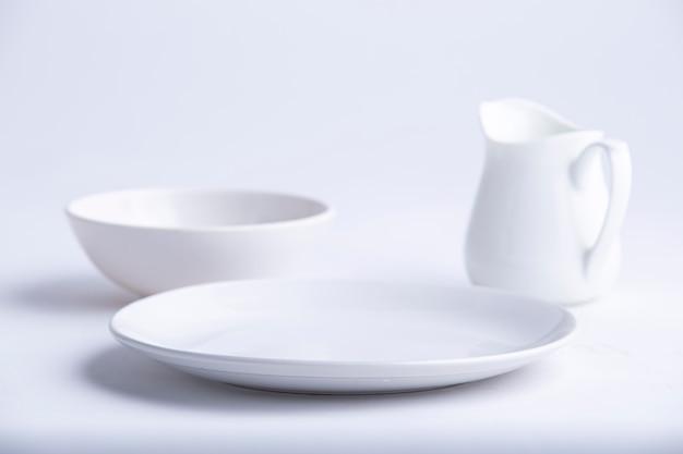 白い食器は、空の白いセラミックプレートボウルとティーポットのさまざまな形をしています