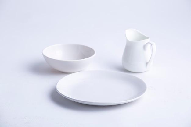 白いテーブルは、空の白いセラミックプレートボウルとティーポットのさまざまな形をしています