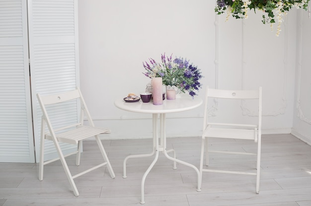White table with a bouquet of flowers and two chairs in the room