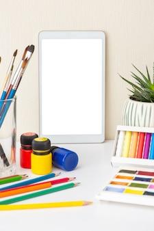Белый стол с цифровым планшетом на белом столе с красочными принадлежностями для рисования и суккулентным горшком. кисти, акварель, мелки, карандаш, акриловые краски. понятие о курсах рисования. макет вертикальный